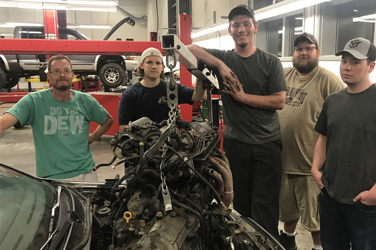 Automotive students working on a car engine.